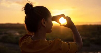 Young woman forming a heart sign with her hands at sunset